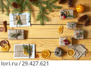 Купить «Hand-made Christmas gifts and congratulations in envelopes decorated with dry fragrant dry orange slices on a wooden background. Top view. Xmas still life», фото № 29427621, снято 25 июля 2018 г. (c) Виктория Катьянова / Фотобанк Лори