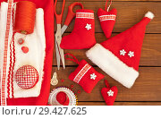 Купить «Making traditional handmade red Christmas toys: Santa hat, hearts, mittens and gift sock. Materials and accessories for needlework. New Year's still life», фото № 29427625, снято 10 декабря 2017 г. (c) Виктория Катьянова / Фотобанк Лори