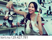 Купить «Glad woman holding many pair of shoes», фото № 29427781, снято 20 апреля 2019 г. (c) Яков Филимонов / Фотобанк Лори