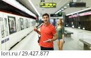 Купить «Man with his girlfriend are standing on platform and choosing route», фото № 29427877, снято 14 июня 2018 г. (c) Яков Филимонов / Фотобанк Лори