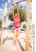 Купить «Woman training on outdoors fitness station», фото № 29427921, снято 26 июня 2018 г. (c) Яков Филимонов / Фотобанк Лори