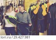 Купить «Positive woman helping man choose new costume for diving», фото № 29427981, снято 25 января 2018 г. (c) Яков Филимонов / Фотобанк Лори