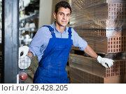 Купить «Portrait of active male in uniform on his workplace in building store.», фото № 29428205, снято 26 июля 2017 г. (c) Яков Филимонов / Фотобанк Лори