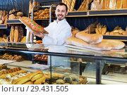 Купить «Man baker showing warm tasty bun in bakery», фото № 29431505, снято 26 января 2017 г. (c) Яков Филимонов / Фотобанк Лори
