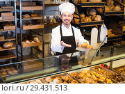 Купить «Positive male pastry maker demonstrating croissant», фото № 29431513, снято 26 января 2017 г. (c) Яков Филимонов / Фотобанк Лори
