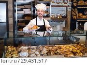 Купить «Male pastry maker demonstrating fresh croissant», фото № 29431517, снято 26 января 2017 г. (c) Яков Филимонов / Фотобанк Лори