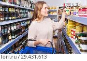 Купить «Woman choosing preserved goods in food store», фото № 29431613, снято 11 апреля 2018 г. (c) Яков Филимонов / Фотобанк Лори