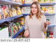 Купить «Woman buyer standing near assortment of grocery food store», фото № 29431621, снято 11 апреля 2018 г. (c) Яков Филимонов / Фотобанк Лори