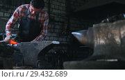Купить «Getting the red-hot detail a form with a hammer. Blacksmith in workroom, anvil», видеоролик № 29432689, снято 19 ноября 2018 г. (c) Константин Шишкин / Фотобанк Лори