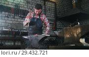 Купить «Blacksmith getting the red-hot detail a form with a hammer. Workroom, anvil», видеоролик № 29432721, снято 19 ноября 2018 г. (c) Константин Шишкин / Фотобанк Лори