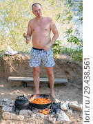 Купить «A young man cooks pilaf in a large cauldron on a fire.», фото № 29438561, снято 15 июля 2017 г. (c) Акиньшин Владимир / Фотобанк Лори