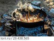 Купить «Uzbek pilaf in large in a cast-iron cauldron is cooked on a fire.», фото № 29438565, снято 15 июля 2017 г. (c) Акиньшин Владимир / Фотобанк Лори