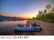 Купить «An inflatable boat with a motor on the shore of a sandy beach against the backdrop of a beautiful sunset.», фото № 29443481, снято 26 июля 2018 г. (c) Акиньшин Владимир / Фотобанк Лори
