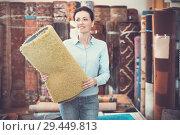 Купить «Cheerful woman customer choosing colored carpet», фото № 29449813, снято 22 ноября 2017 г. (c) Яков Филимонов / Фотобанк Лори