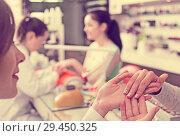 Купить «Manicurist inspecting female hands», фото № 29450325, снято 28 апреля 2017 г. (c) Яков Филимонов / Фотобанк Лори