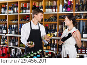 Купить «Seller helping woman customer with bottle of wine», фото № 29456201, снято 19 декабря 2018 г. (c) Яков Филимонов / Фотобанк Лори
