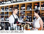 Купить «portrait of male seller showing bottle of wine to female customer in wine shop», фото № 29456205, снято 6 июня 2020 г. (c) Яков Филимонов / Фотобанк Лори