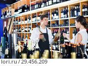 Купить «Seller helping woman customer with bottle of wine», фото № 29456209, снято 19 декабря 2018 г. (c) Яков Филимонов / Фотобанк Лори