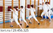 Купить «Adult teenages fencers practicing technique on cushions», фото № 29456325, снято 30 мая 2018 г. (c) Яков Филимонов / Фотобанк Лори