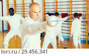 Купить «Adult man fencer practicing effective fencing techniques in training room», фото № 29456341, снято 30 мая 2018 г. (c) Яков Филимонов / Фотобанк Лори