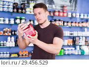 Купить «Young muscular guy reading content label, choosing sport nutrition», фото № 29456529, снято 12 апреля 2018 г. (c) Яков Филимонов / Фотобанк Лори