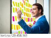 Купить «Young handsome employee with many conflicting priorities», фото № 29458161, снято 15 августа 2018 г. (c) Elnur / Фотобанк Лори