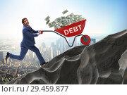 Купить «Businessman pushing wheelbarrow uphill in debt loan concept», фото № 29459877, снято 22 ноября 2018 г. (c) Elnur / Фотобанк Лори