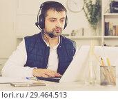 Купить «Young man call centre operator with headphones working», фото № 29464513, снято 25 декабря 2017 г. (c) Яков Филимонов / Фотобанк Лори