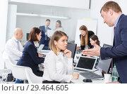 Купить «Unhappy girl sitting at laptop in coworking space while dissatisfied businessman», фото № 29464605, снято 21 апреля 2018 г. (c) Яков Филимонов / Фотобанк Лори