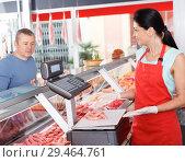 Купить «Female seller weighing sausages for customer», фото № 29464761, снято 22 июня 2018 г. (c) Яков Филимонов / Фотобанк Лори