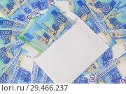 Купить «Белый почтовый конверт с новыми российскими купюрами на фоне денег», фото № 29466237, снято 11 ноября 2018 г. (c) Наталья Гармашева / Фотобанк Лори