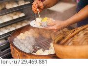 Купить «A street vendor prepares steamed Dim Sum (Shumai/Shaomai) in the Jalan Petaling street market, Chinatown, Kuala Lumpur.», фото № 29469881, снято 17 июня 2018 г. (c) age Fotostock / Фотобанк Лори