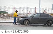 Купить «Car Trouble. Winter, cold weather. A young woman walks out of the car and opens the hood», видеоролик № 29470565, снято 27 января 2020 г. (c) Константин Шишкин / Фотобанк Лори