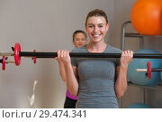 Купить «Young women training with barbells together in fitness class.», фото № 29474341, снято 11 ноября 2018 г. (c) Pavel Biryukov / Фотобанк Лори