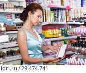 Купить «Woman with schemes of nail polish in cosmetics shop», фото № 29474741, снято 21 июня 2018 г. (c) Яков Филимонов / Фотобанк Лори