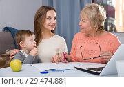 Купить «Woman is talking her mother how to fill utility bills with laptop», фото № 29474881, снято 15 февраля 2018 г. (c) Яков Филимонов / Фотобанк Лори