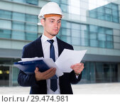 Купить «Designer in suit and hat with folder is looking into documents with project», фото № 29474981, снято 3 июня 2017 г. (c) Яков Филимонов / Фотобанк Лори