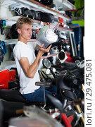 Купить «Young motorcyclist choosing new helmet for motorcycle», фото № 29475081, снято 17 июля 2017 г. (c) Яков Филимонов / Фотобанк Лори
