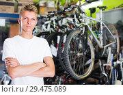 Купить «young serious male standing near the cycle in the shop», фото № 29475089, снято 17 июля 2017 г. (c) Яков Филимонов / Фотобанк Лори