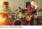 Купить «Guy guitar player and singer practicing with band members in re», фото № 29475261, снято 26 октября 2018 г. (c) Яков Филимонов / Фотобанк Лори