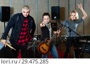 Купить «Three bandmates posing together with musical instruments in rehearsal room», фото № 29475285, снято 26 октября 2018 г. (c) Яков Филимонов / Фотобанк Лори