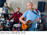 Купить «Rehearsal of music group. Band leader playing guitar and singing with his musicians in recording studio», фото № 29475313, снято 26 октября 2018 г. (c) Яков Филимонов / Фотобанк Лори