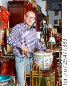 Купить «Experienced appraiser of antiques shop measuring antique vase while determining value», фото № 29477389, снято 15 мая 2018 г. (c) Яков Филимонов / Фотобанк Лори