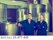 Купить «Two cheerful men in uniforms standing in winery fermentation compartment», фото № 29477445, снято 19 января 2019 г. (c) Яков Филимонов / Фотобанк Лори
