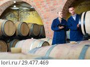 Купить «Two adult men winery employees writing note», фото № 29477469, снято 19 января 2019 г. (c) Яков Филимонов / Фотобанк Лори