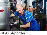 Купить «Mature male technician fitting new car tyre», фото № 29477529, снято 19 сентября 2019 г. (c) Яков Филимонов / Фотобанк Лори