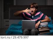 Купить «Young handsome student preparing for exams at night», фото № 29479997, снято 18 сентября 2018 г. (c) Elnur / Фотобанк Лори