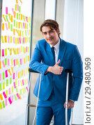 Купить «Young handsome man with crutches in conflicting priorities conce», фото № 29480969, снято 25 августа 2018 г. (c) Elnur / Фотобанк Лори