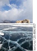 Купить «Baikal Lake in winter. Strait Small Sea (Maloe More). Beautiful smooth ice with cracks near the stone island of Borga-Dagan on the background of cumulus clouds», фото № 29484957, снято 1 марта 2015 г. (c) Виктория Катьянова / Фотобанк Лори