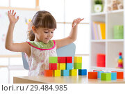 Купить «Little girl build block toys at home or daycare. Kid playing with color cubes. Educational toys for preschool and kindergarten children.», фото № 29484985, снято 16 декабря 2018 г. (c) Оксана Кузьмина / Фотобанк Лори